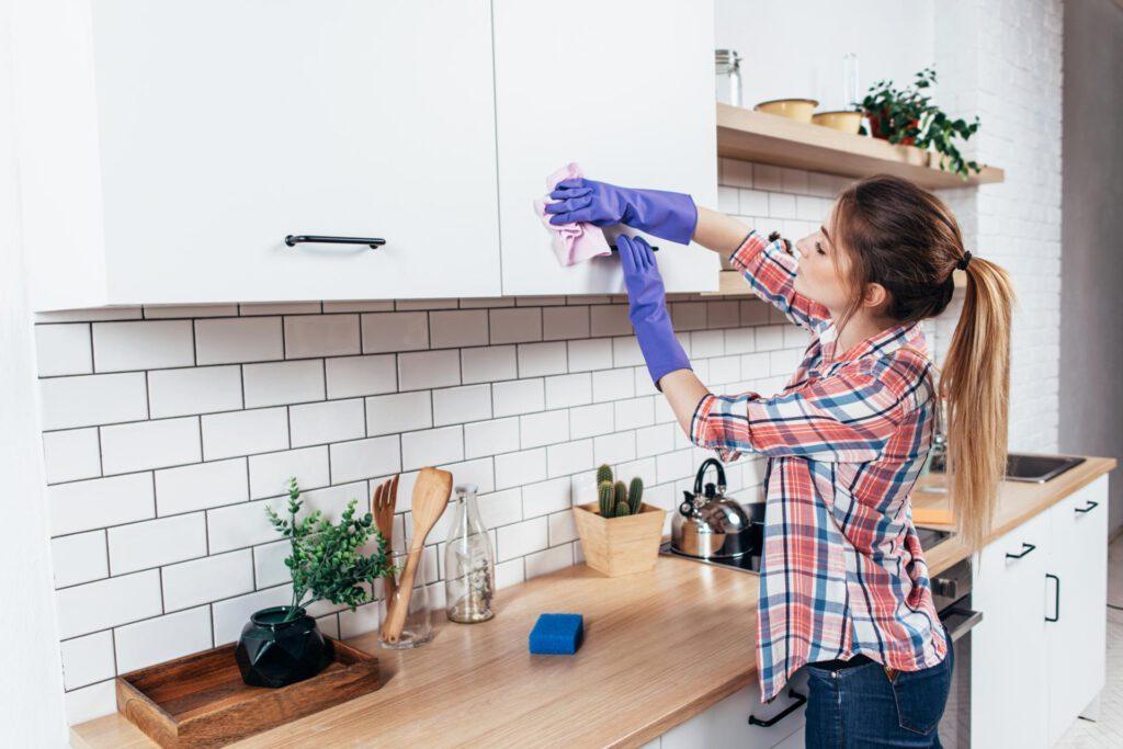 Junge Frau putzt die Küche