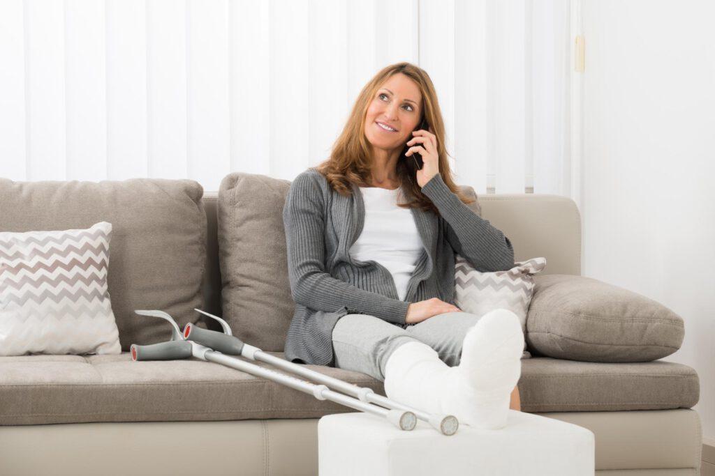 Frau mit gebrochenem Bein telefoniert