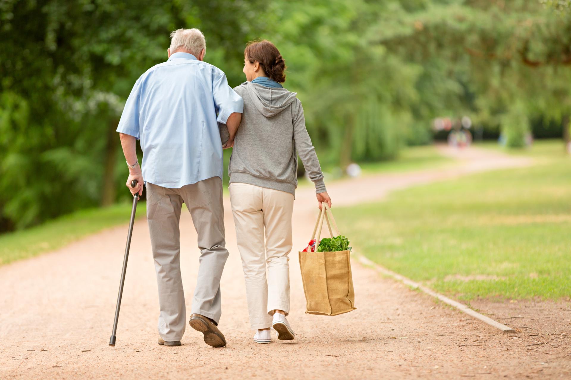 Frau hilft älteren Mann